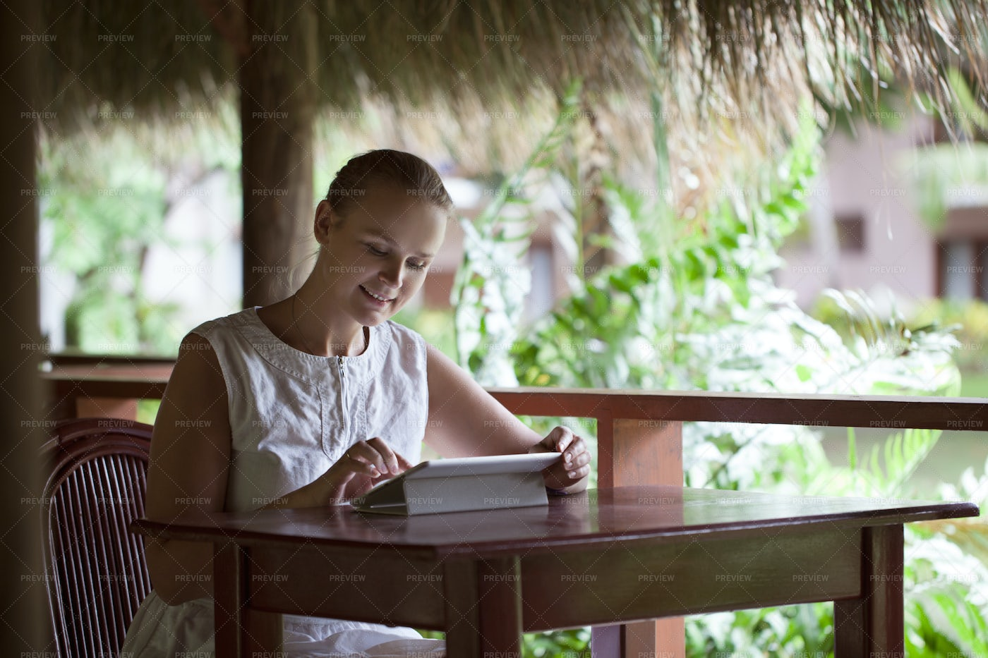 On Tablet In Tropical Cafe: Stock Photos