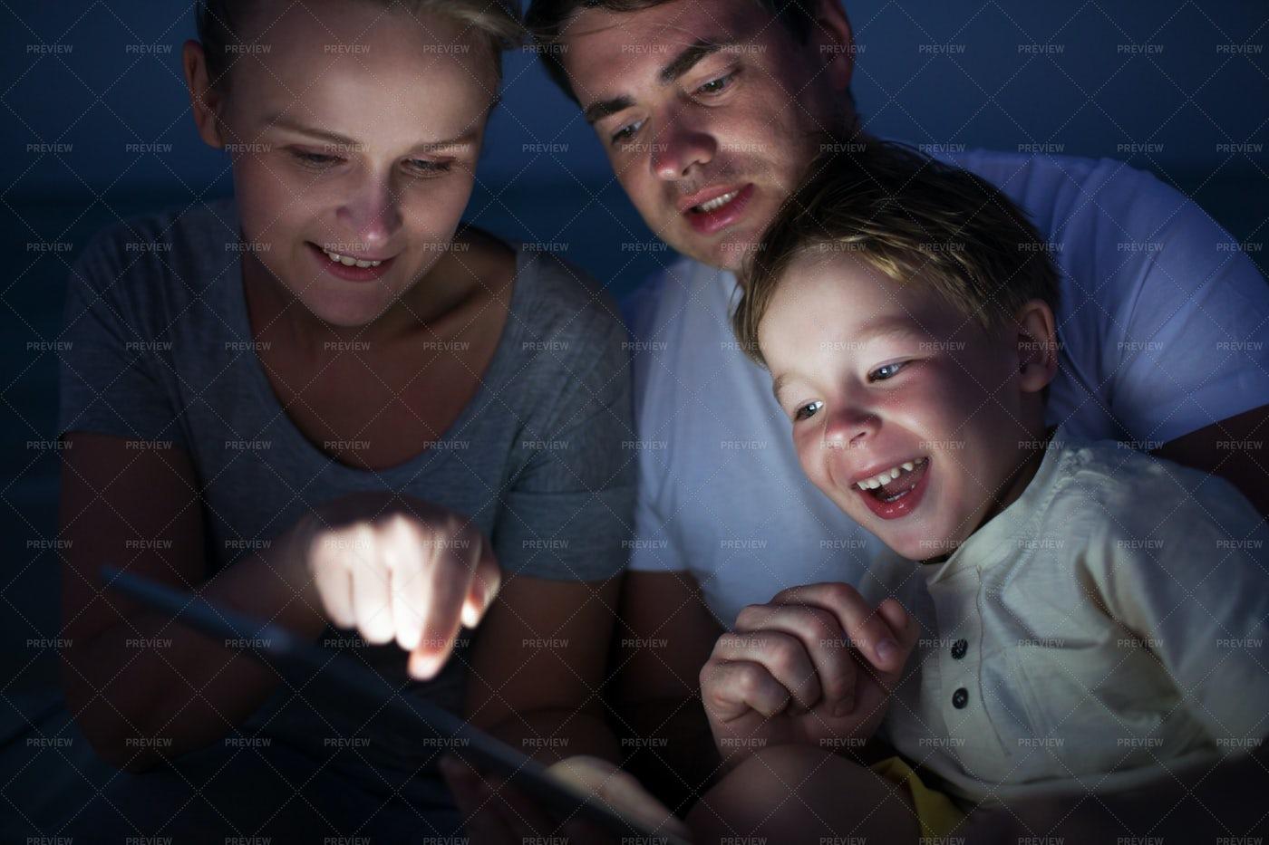 Family Using Tablet At Night: Stock Photos