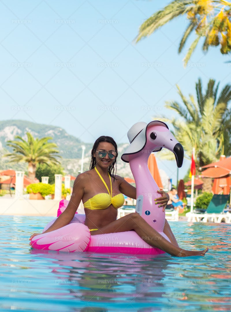 Girl On Flamingo Pool Float: Stock Photos