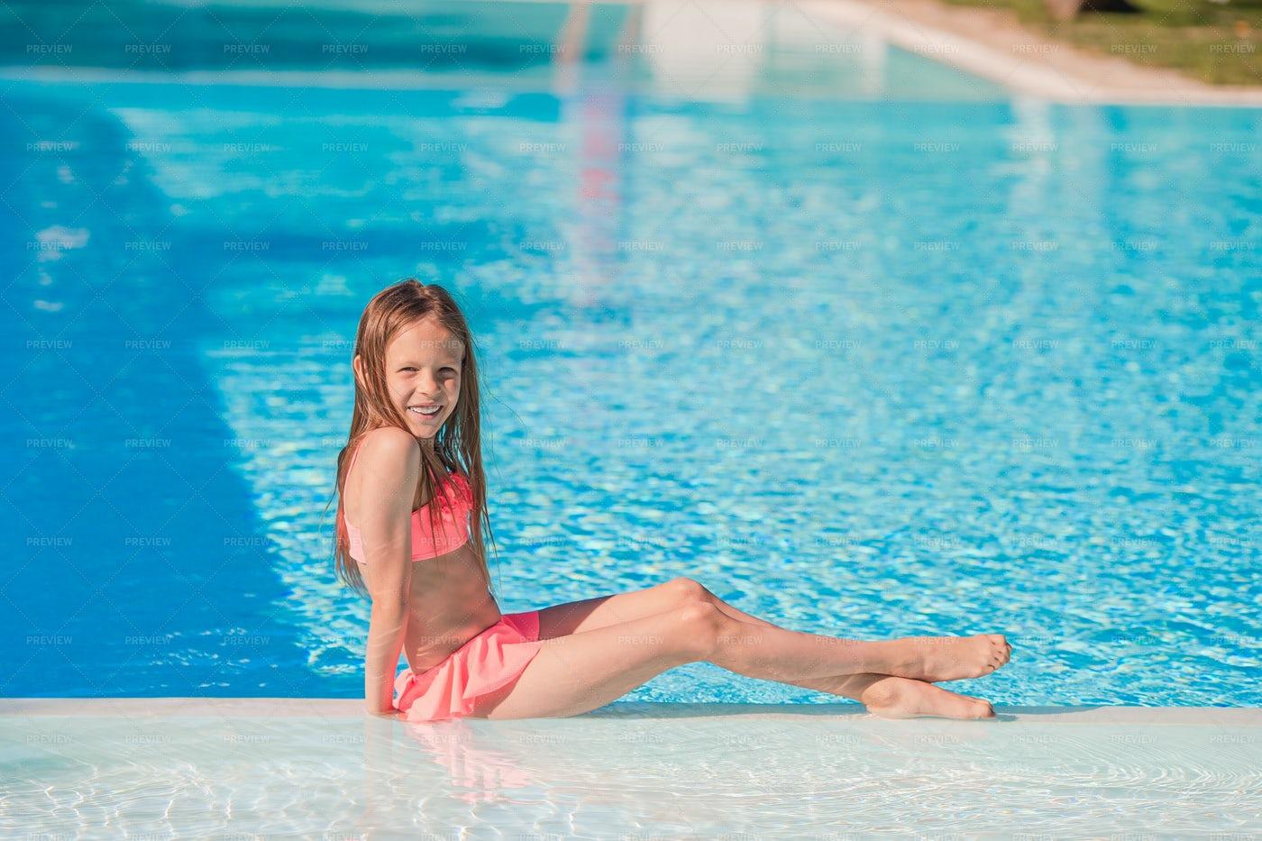 Little Girl Sitting Poolside: Stock Photos