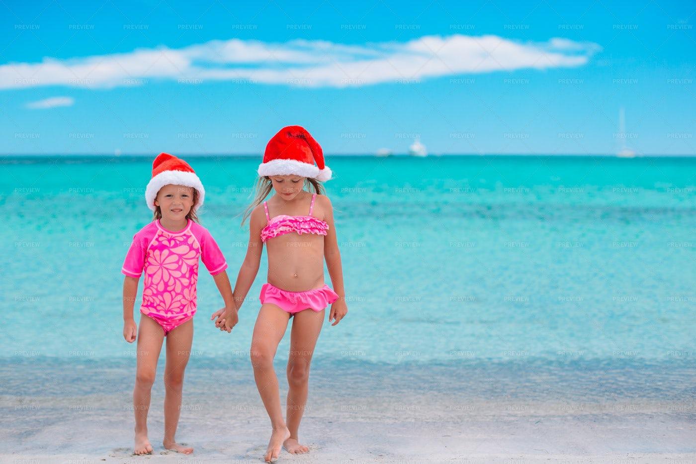 Sisters Wearing Santa Hats On Shore: Stock Photos