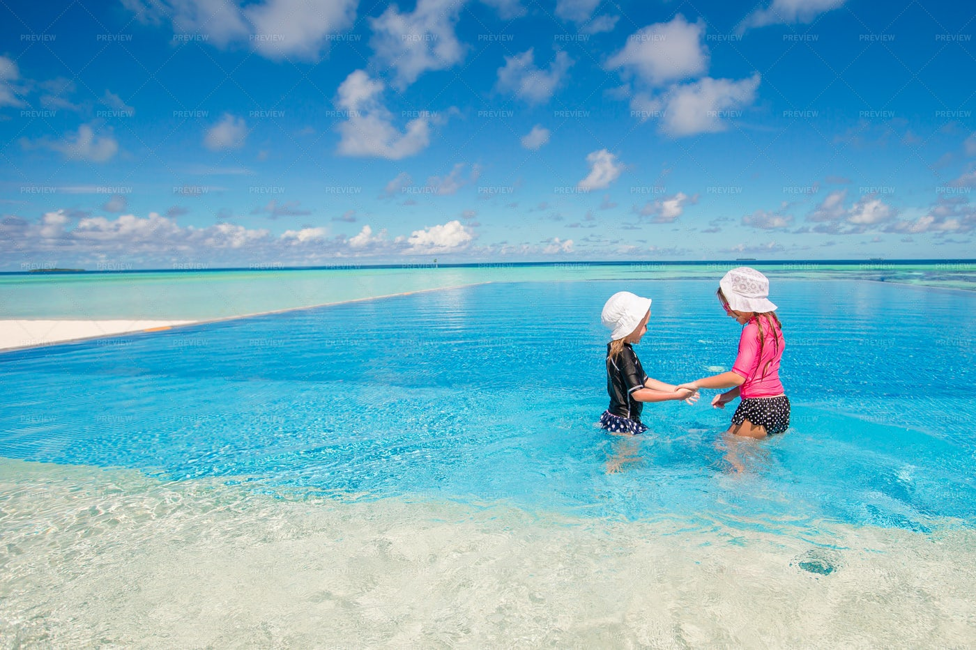 Sisters Playing In Infinity Pool: Stock Photos