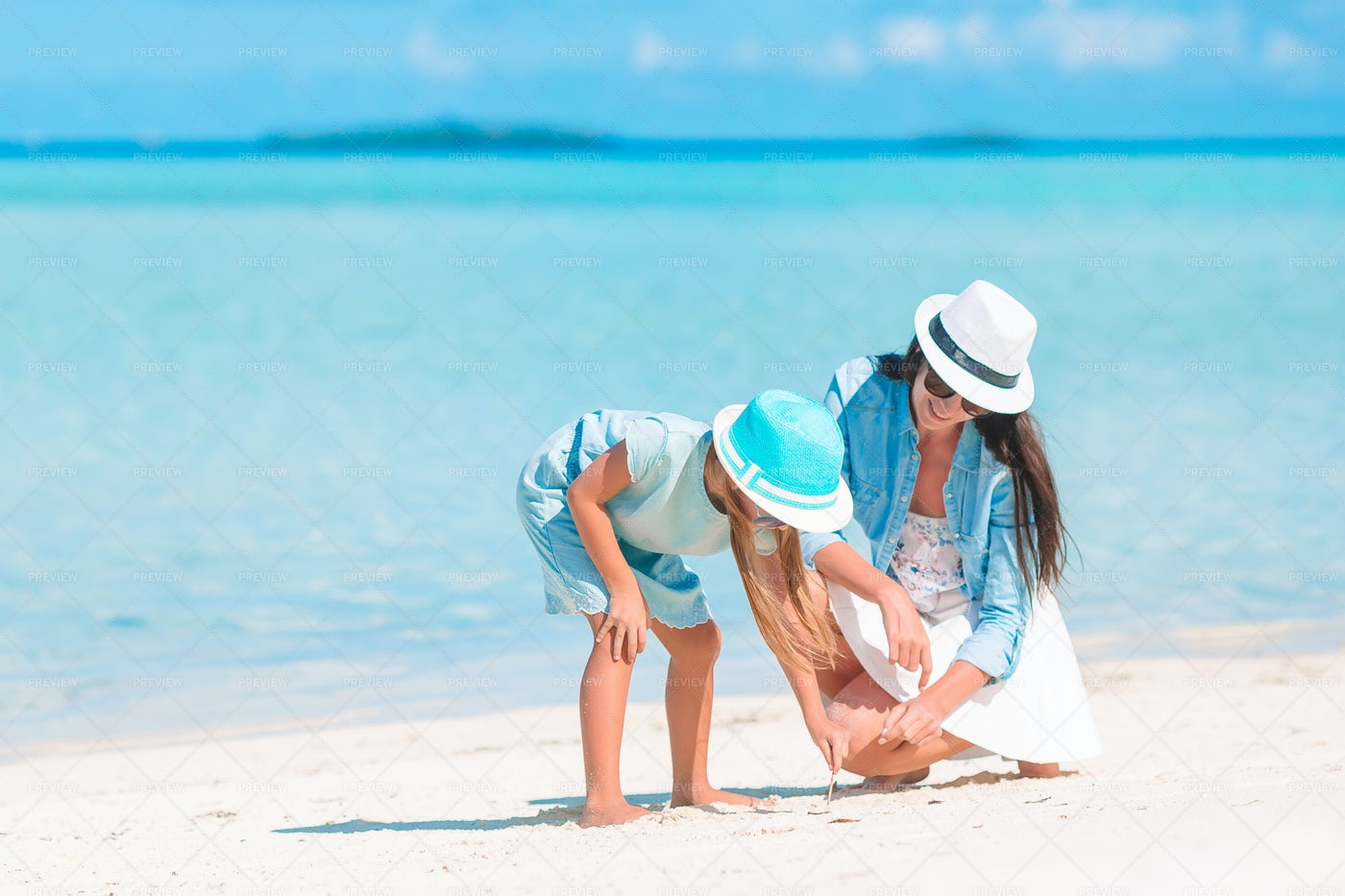 Mom And Girl Drawing In The Sand: Stock Photos