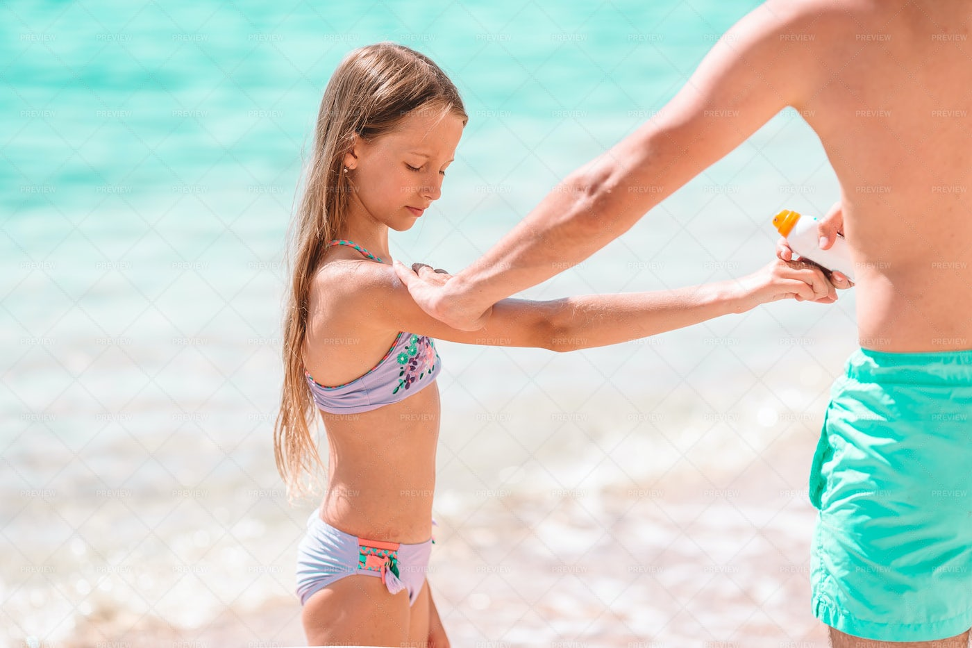 Father Applying Sunscreen To Daughter: Stock Photos
