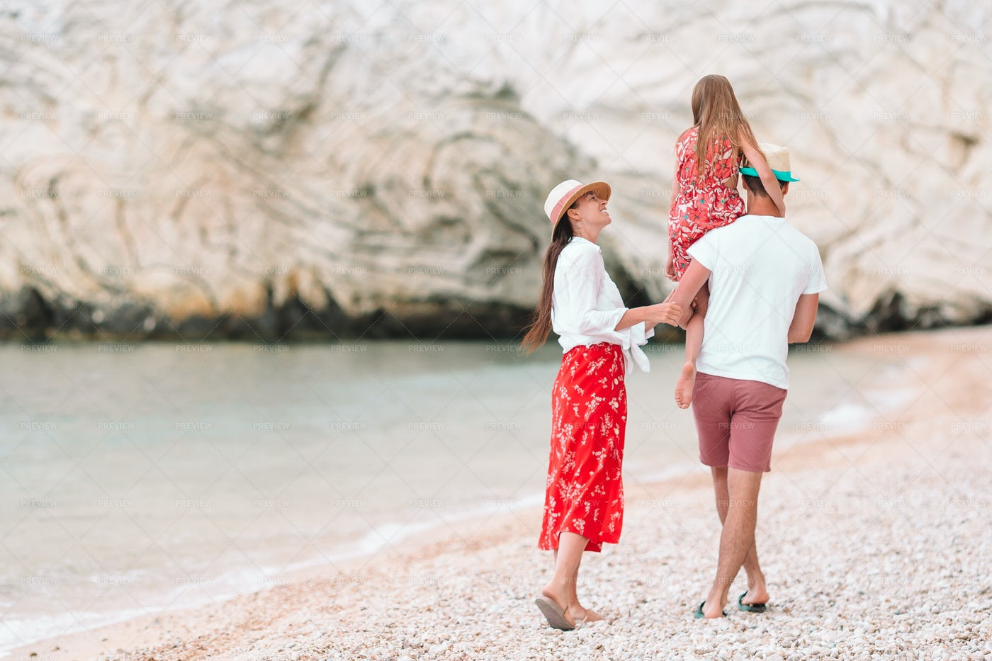 Young Family Walking On Beach: Stock Photos