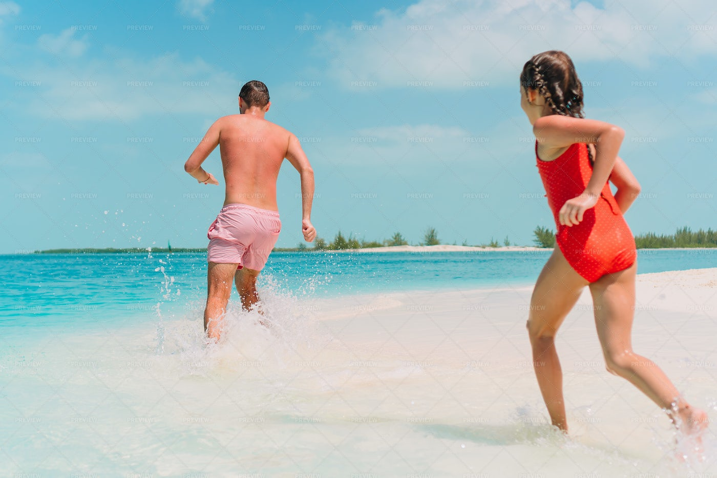 Chasing Dad Into The Water: Stock Photos