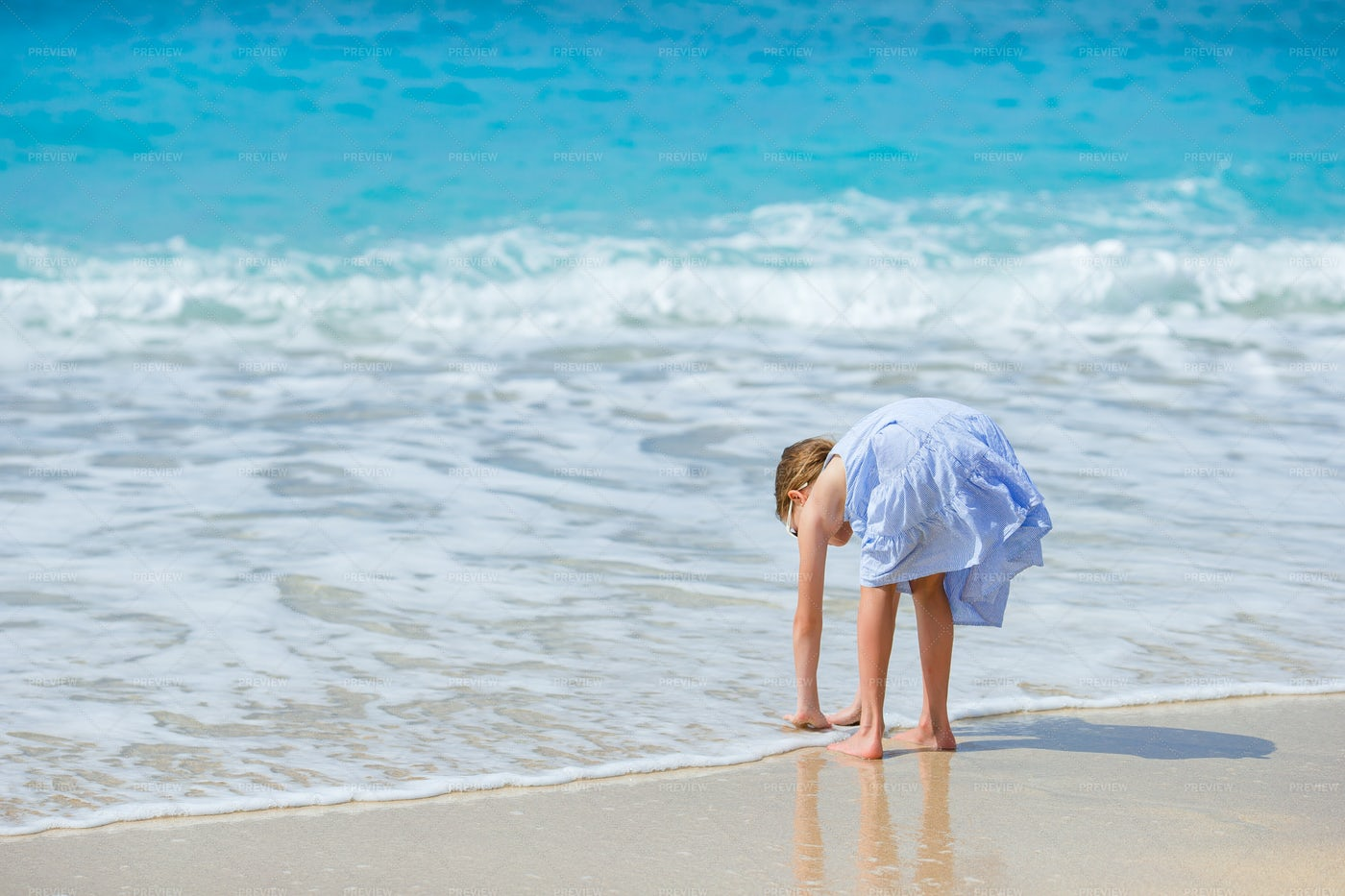 Girl Touching Water On The Beach: Stock Photos