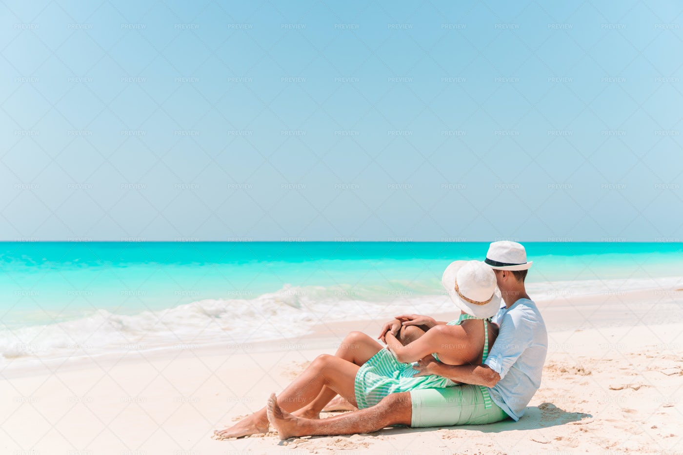 Couple Curled Up On The Beach: Stock Photos