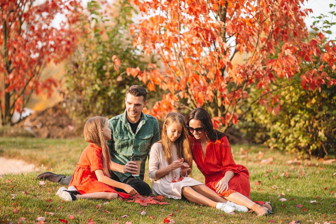 Family Sitting In Autumn Park: Stock Photos