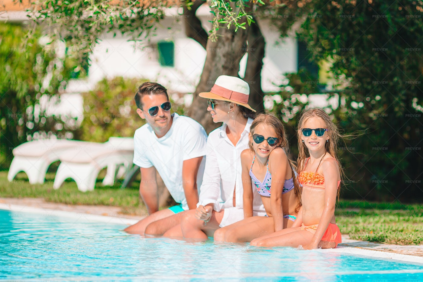 Family Sitting By The Pool: Stock Photos