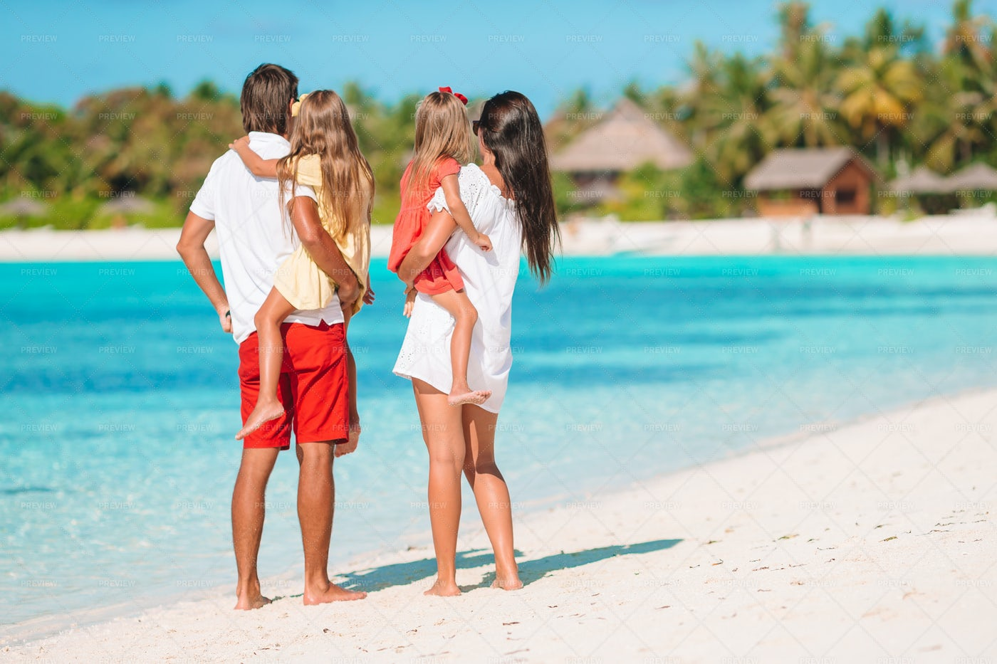 Parents Holding Kids On Beach: Stock Photos