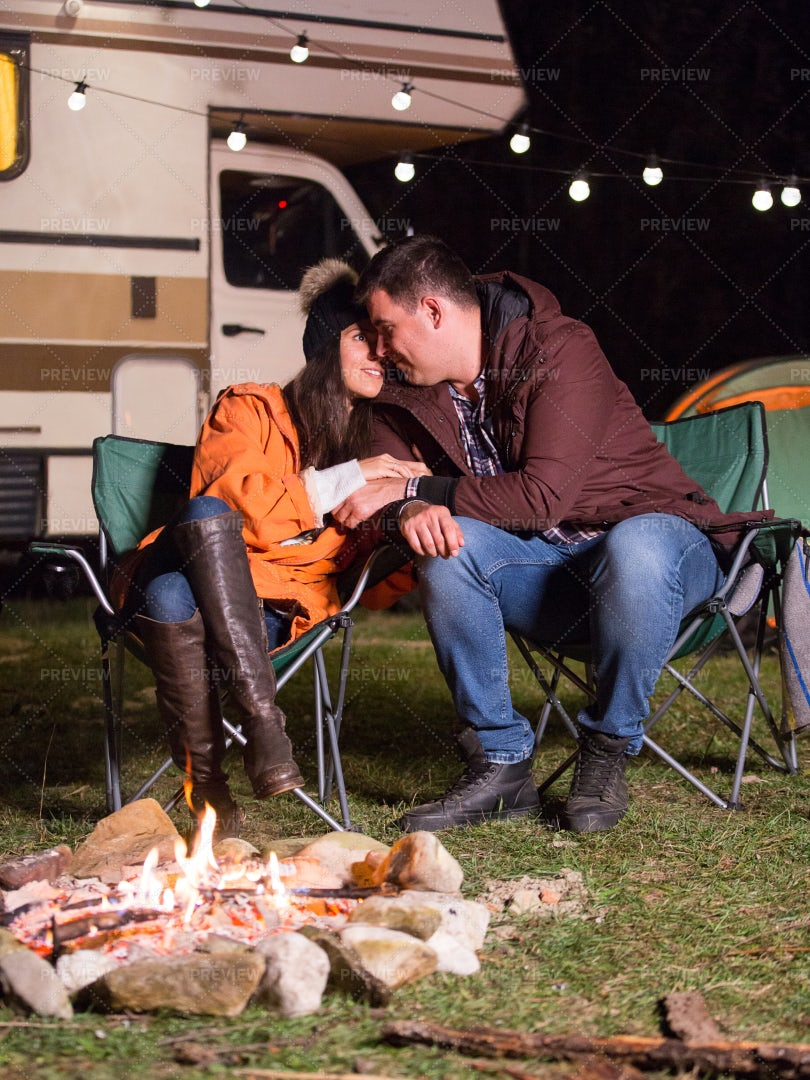 Couple Snuggling By Campfire: Stock Photos