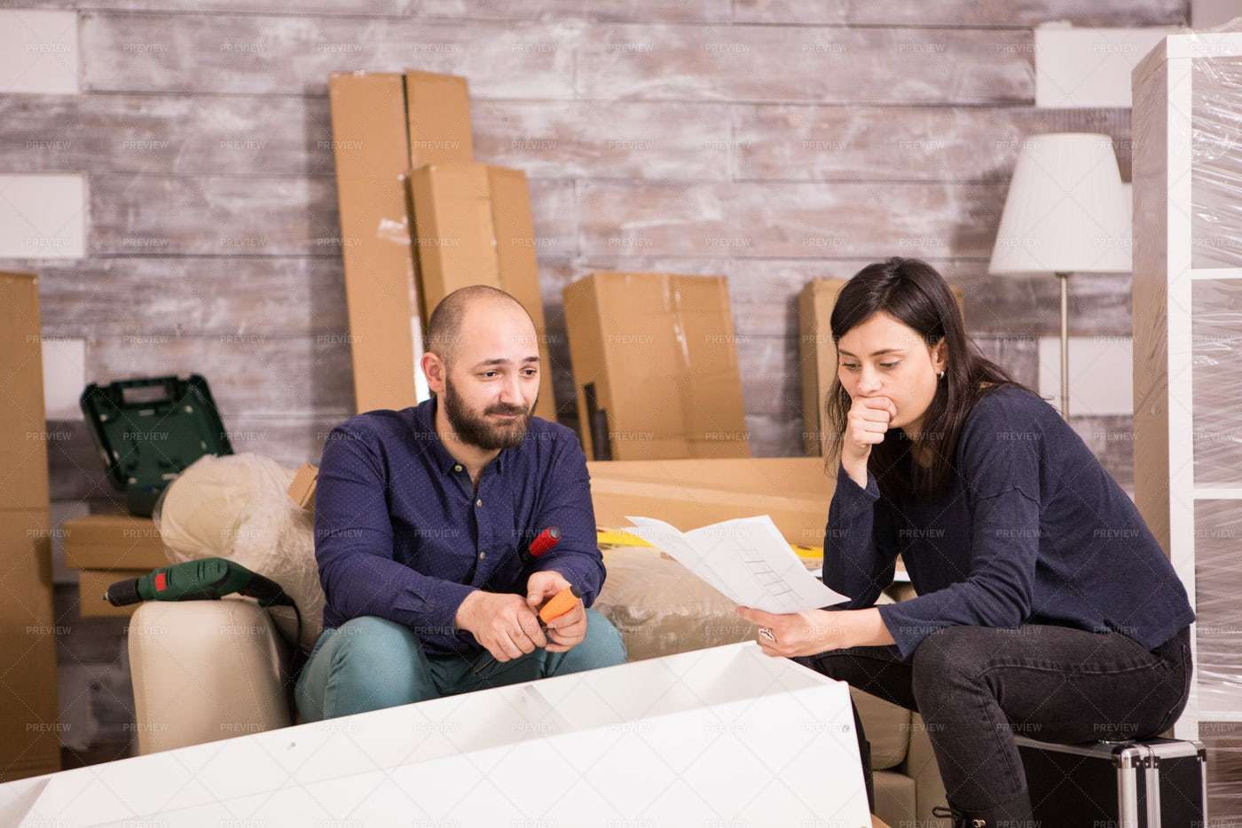 Hopeless Couple Assembling Furniture: Stock Photos