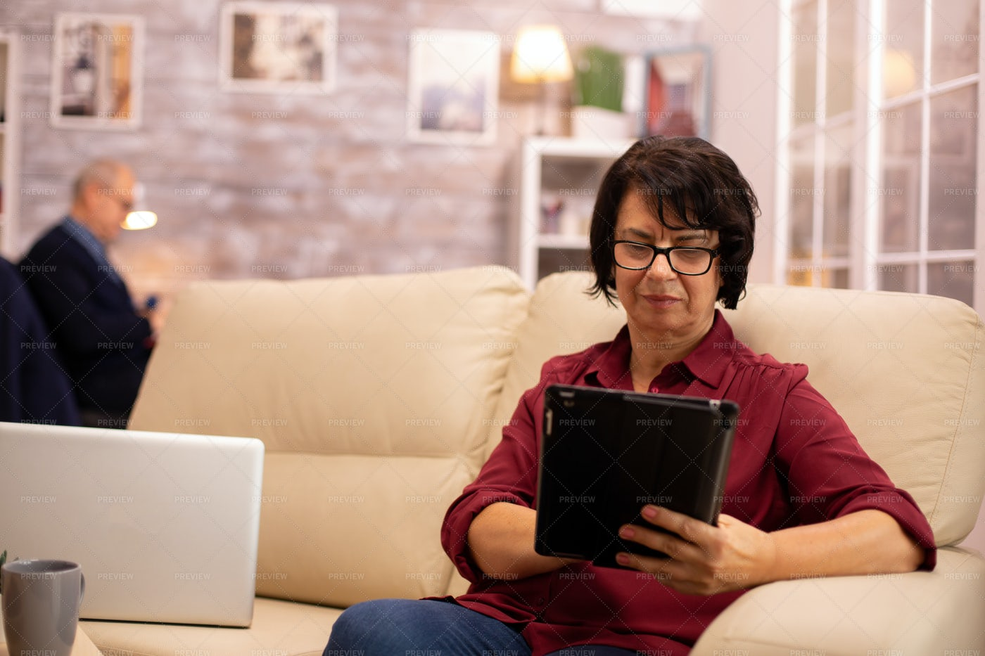 Old Elderly Woman Working On The Sofa: Stock Photos