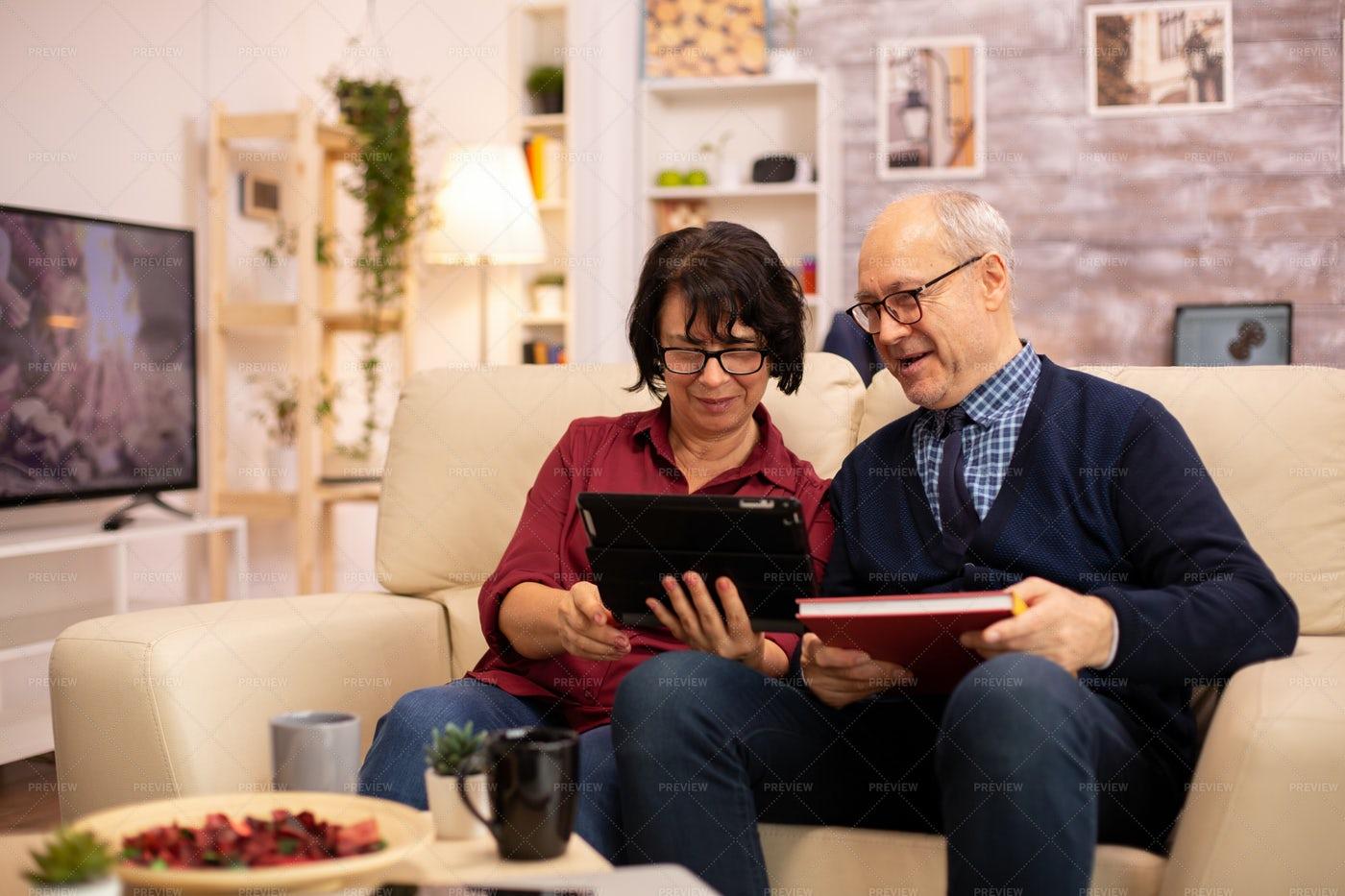 An Elderly Couple Using A Digital Tablet: Stock Photos