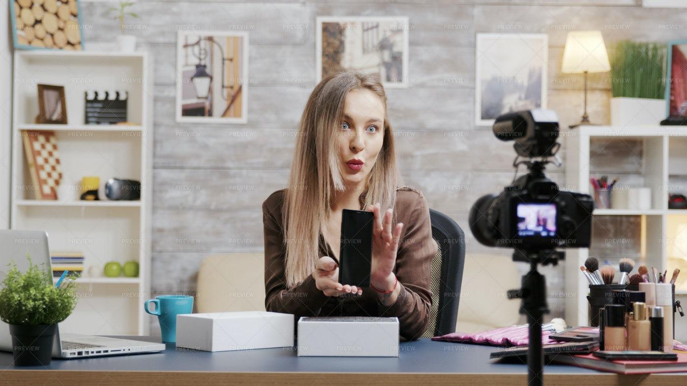 Influencer Reviewing Phone: Stock Photos