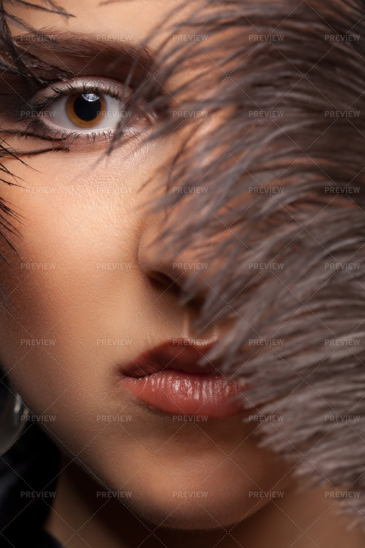 Woman With Feathers In Her Face: Stock Photos