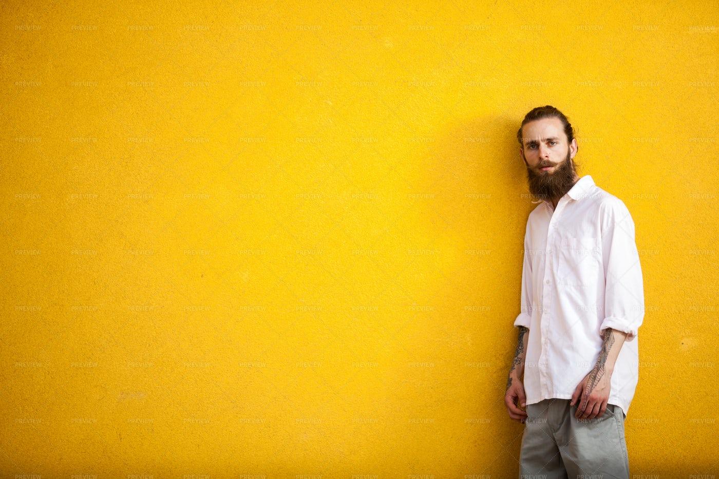 Tattooed Man Against Yellow Wall: Stock Photos