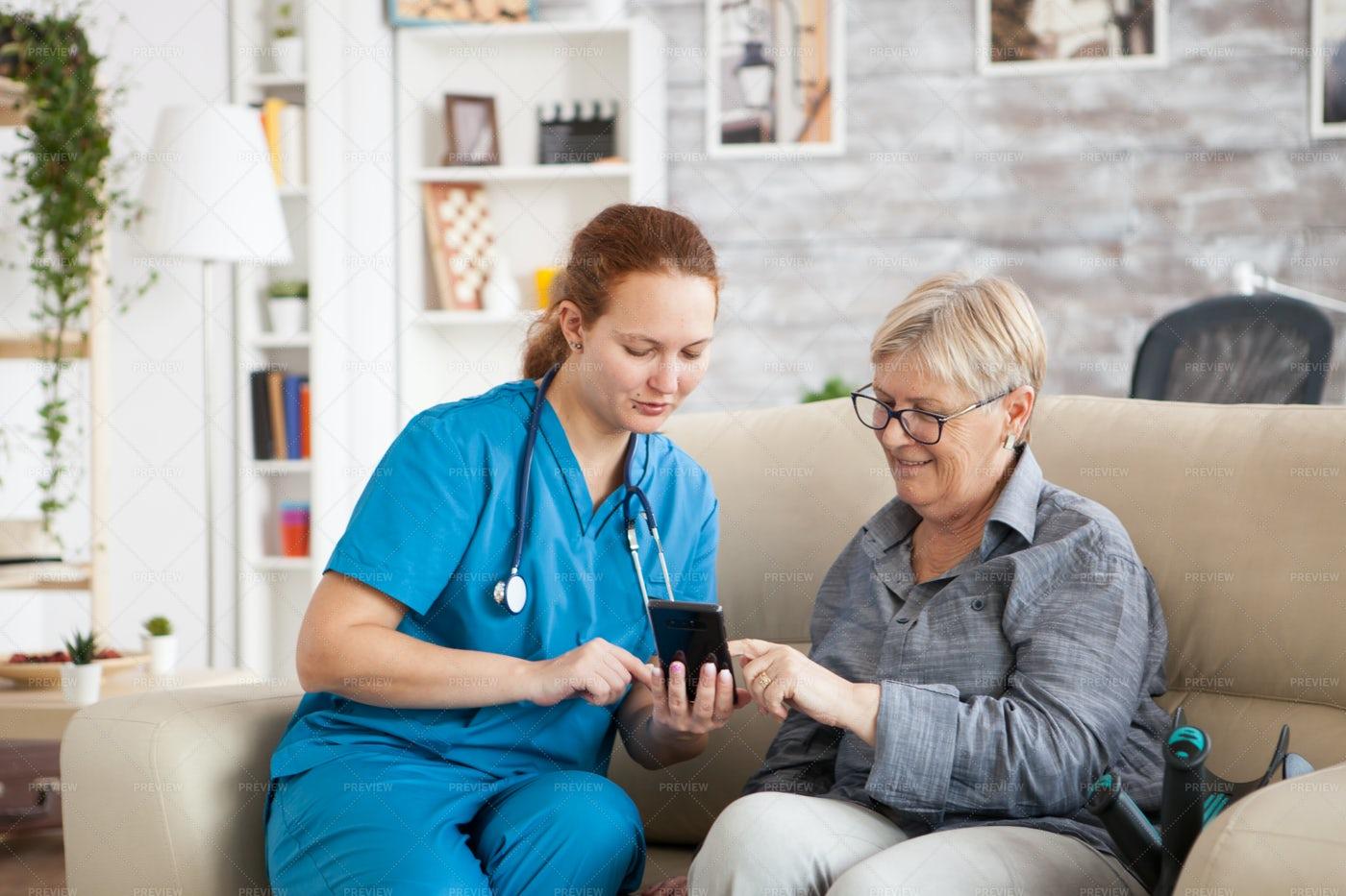 Nurse Helping Woman With App: Stock Photos