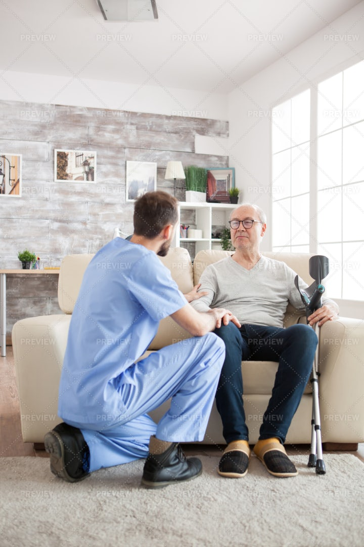 Young Doctor Holding Old Man Arm: Stock Photos