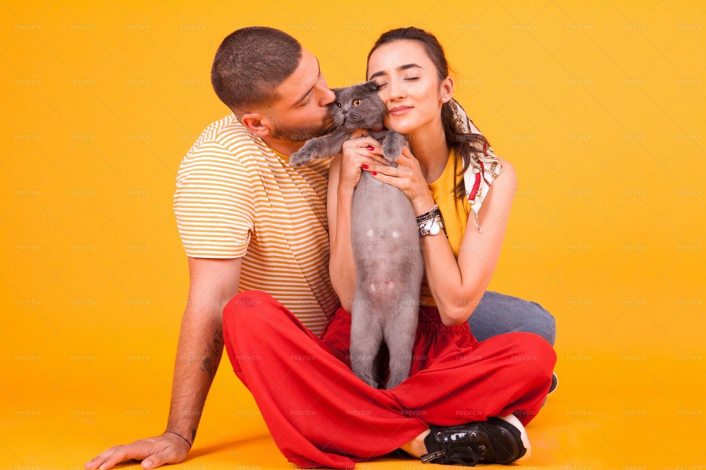 Couple Kissing Their Pet Cat: Stock Photos