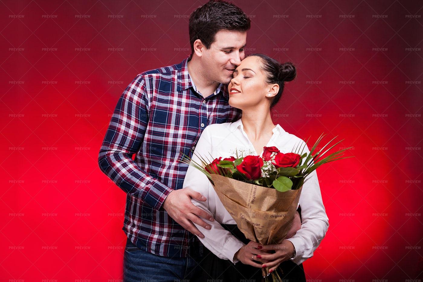 Man Embracing Woman With Roses: Stock Photos
