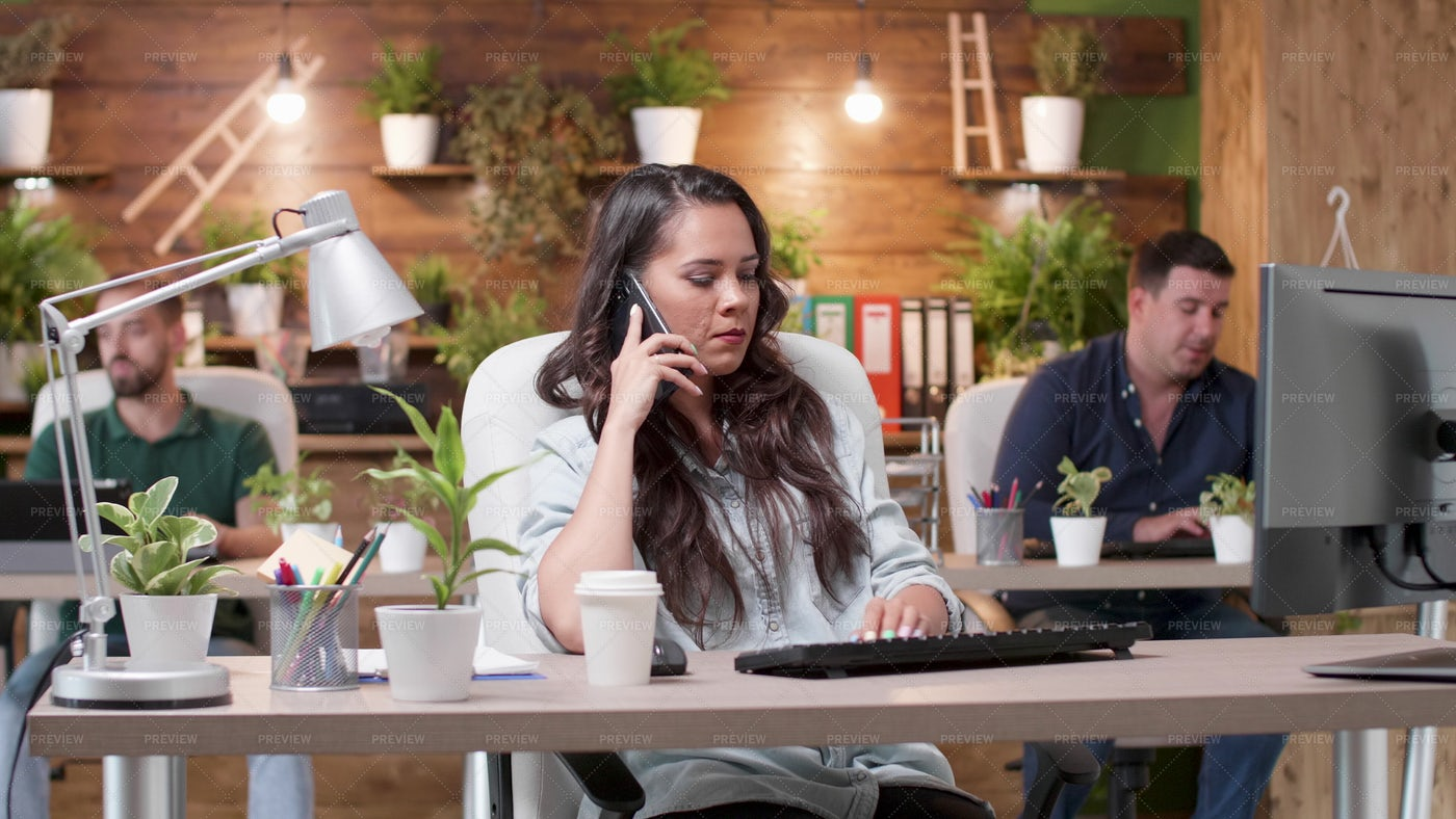 At The Phone In A Green Office: Stock Photos
