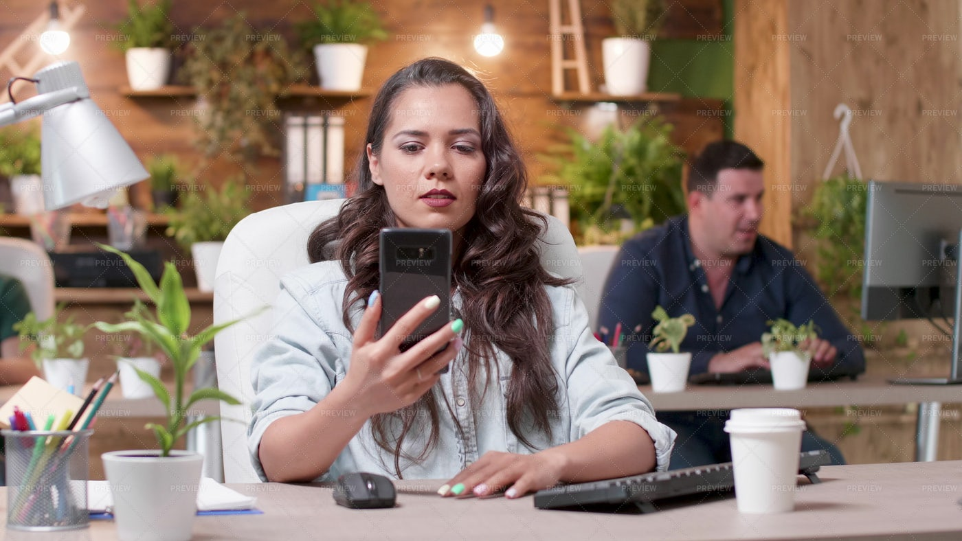 Looking At Phone In Office: Stock Photos