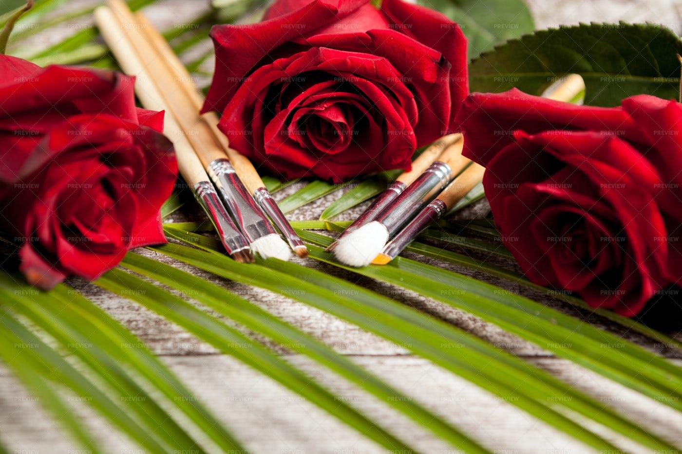 A Set Of Makeup Brushes Next To Roses: Stock Photos