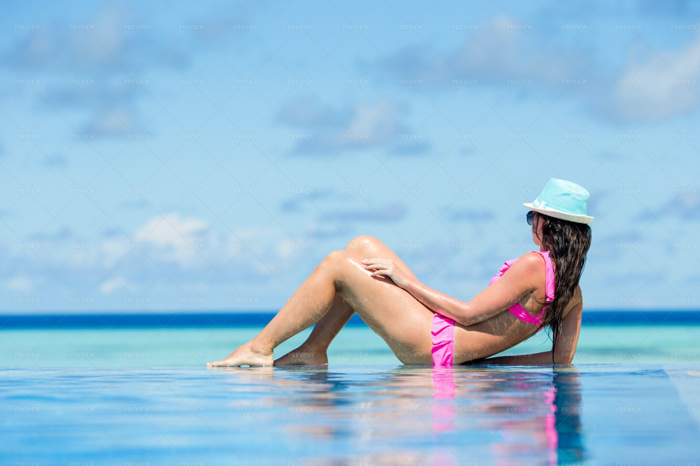 Tanning In Infinity Pool: Stock Photos