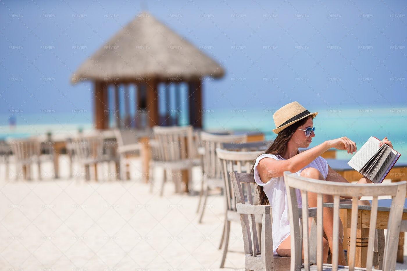 Reading At Beachfront Restaurant: Stock Photos