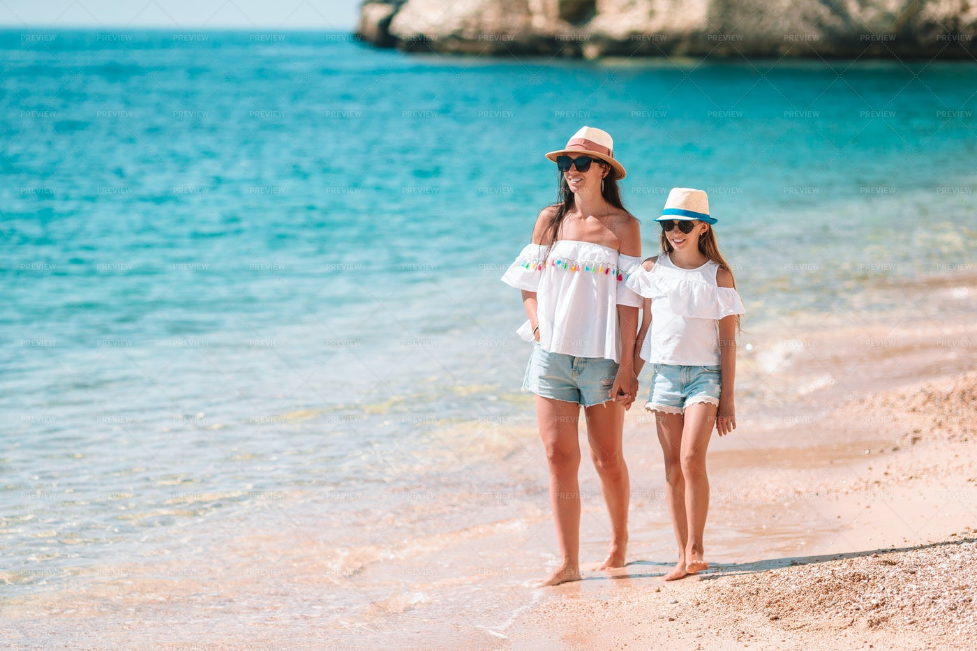 Mom And Daughter Walking In The Sand: Stock Photos