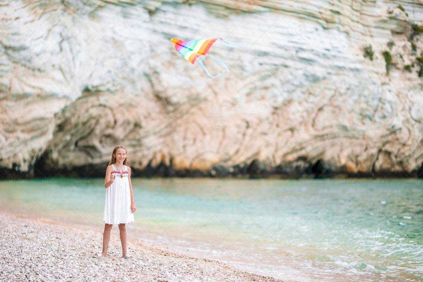 Little Girl Flying A Kite On The Beach: Stock Photos