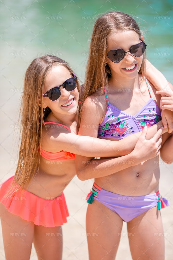 Sisters Embracing On The Beach: Stock Photos