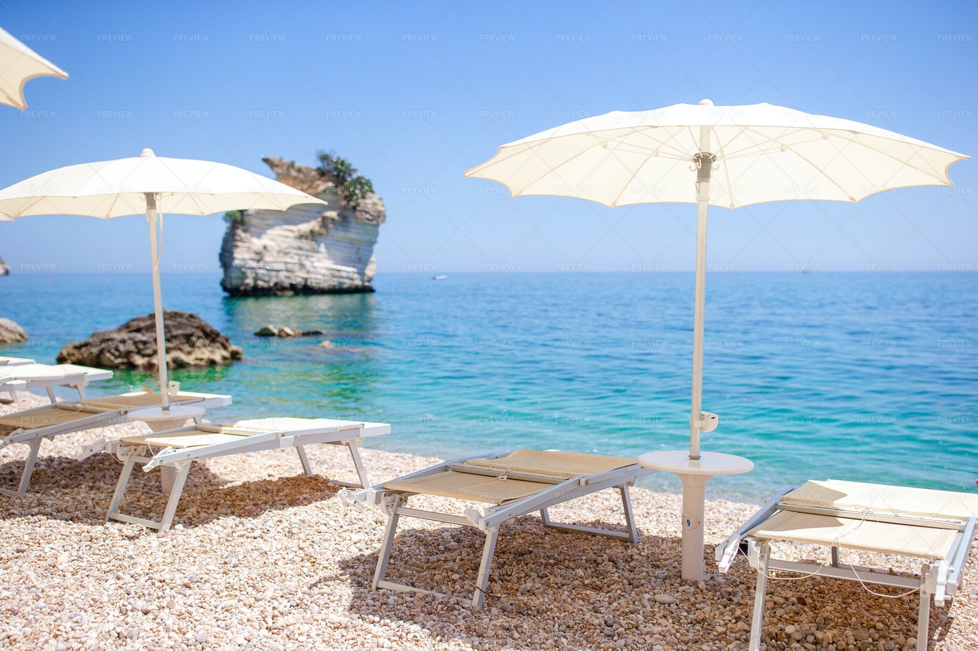 White Umbrella And Sunbeds: Stock Photos