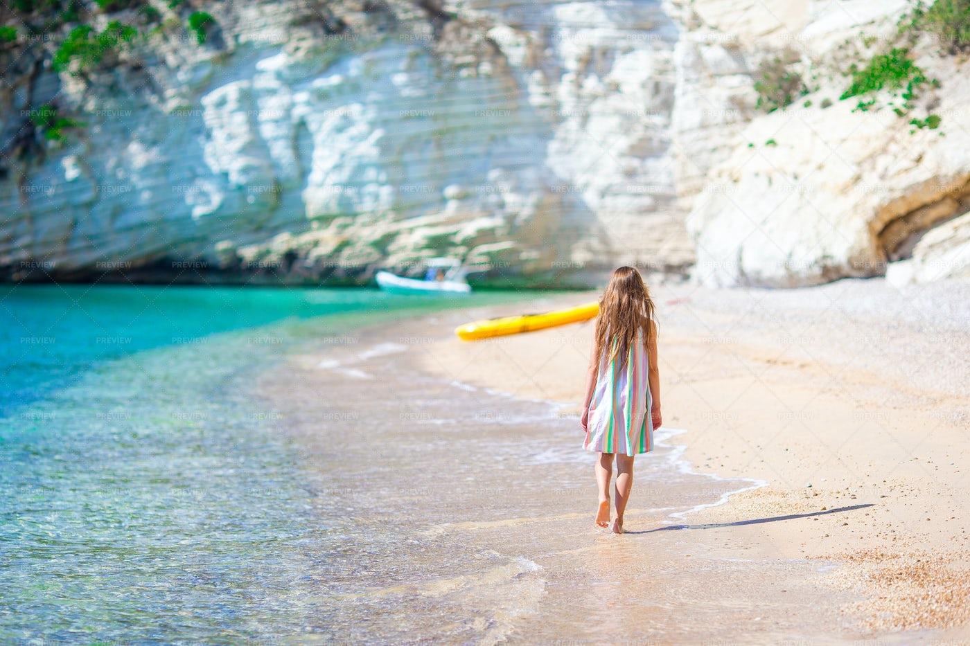 Little Girl Walking On The Seashore: Stock Photos