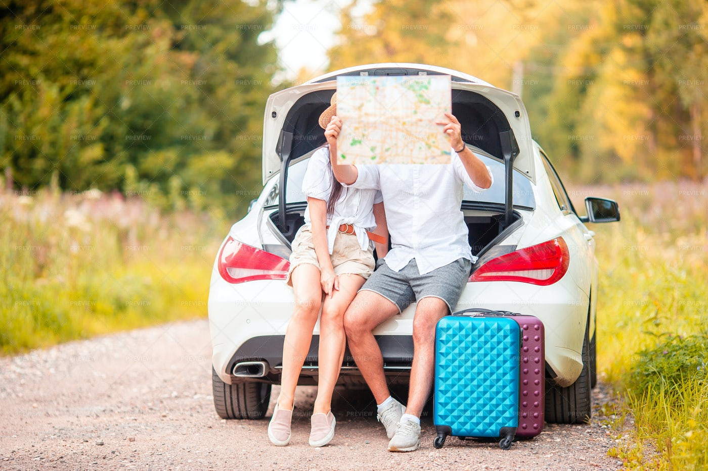 Reading A Map In The Car Trunk: Stock Photos