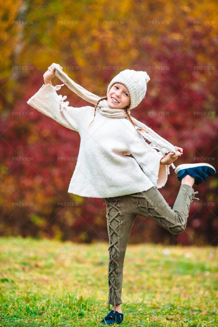 Little Girl Playing In An Autumn Park: Stock Photos