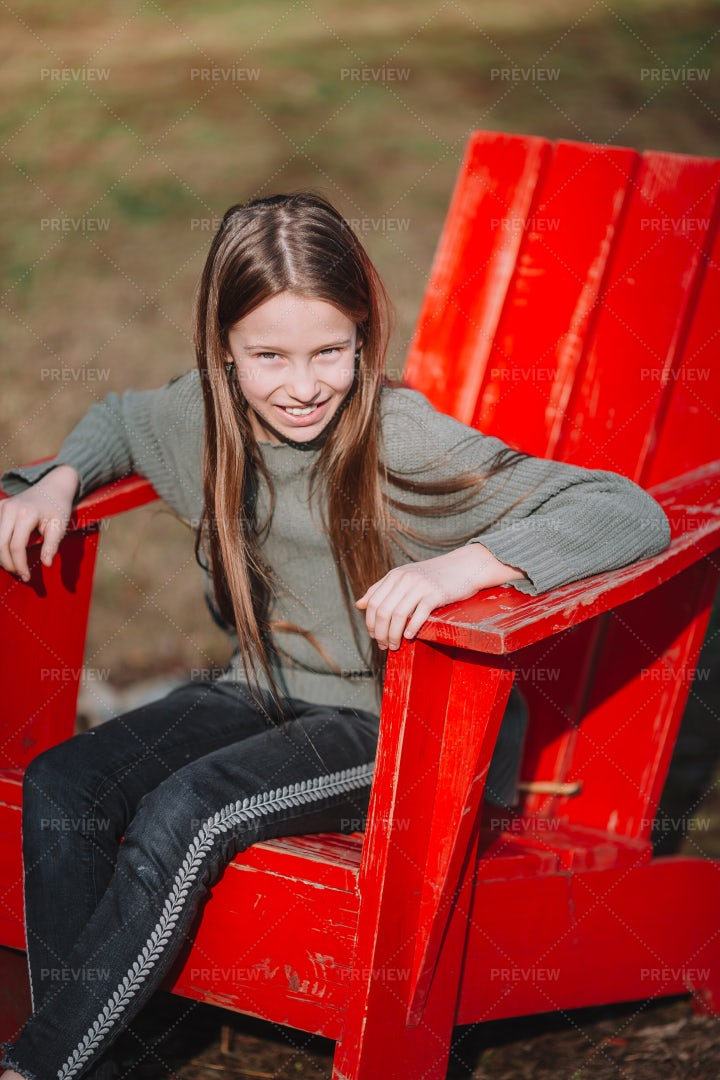 Girl In Red Adirondack Chair: Stock Photos