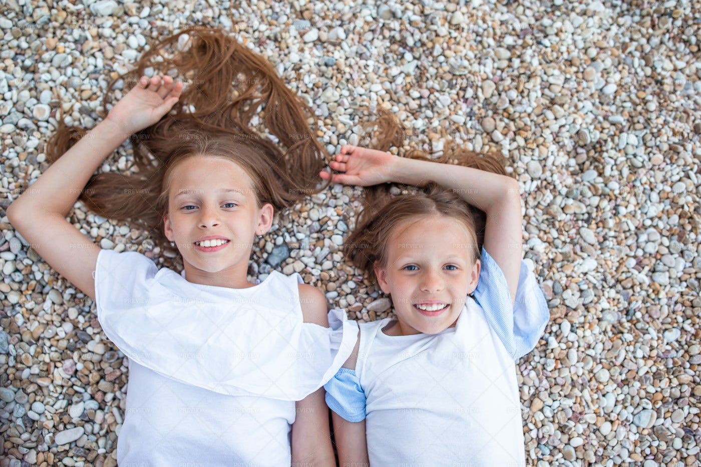 Sisters Lying On Pebbles: Stock Photos