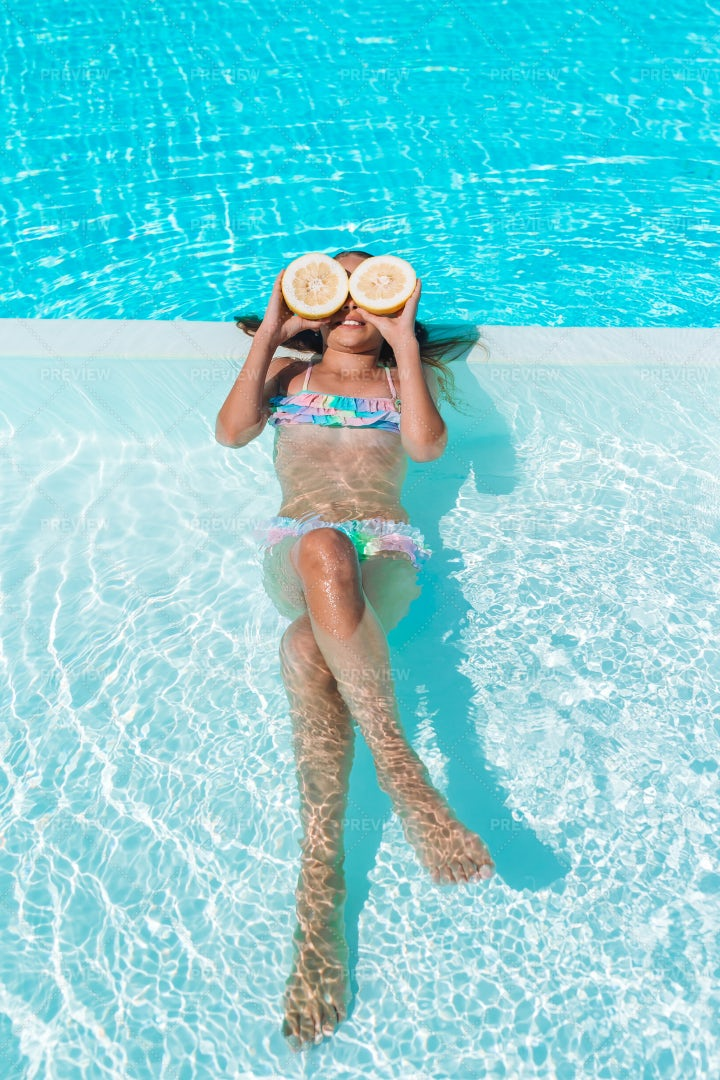 Kid In Pool With Lemons: Stock Photos
