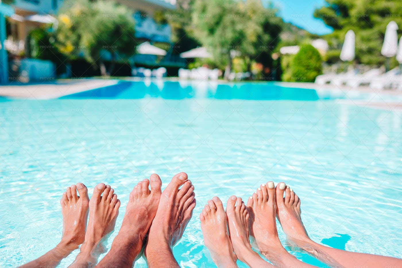 Four People's Legs By Pool: Stock Photos