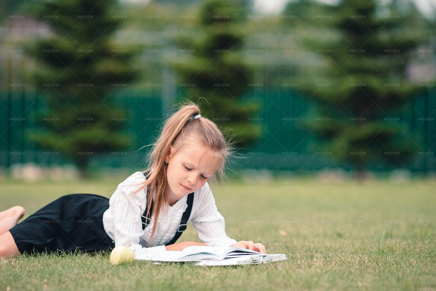 Child Reading A Book Outside: Stock Photos
