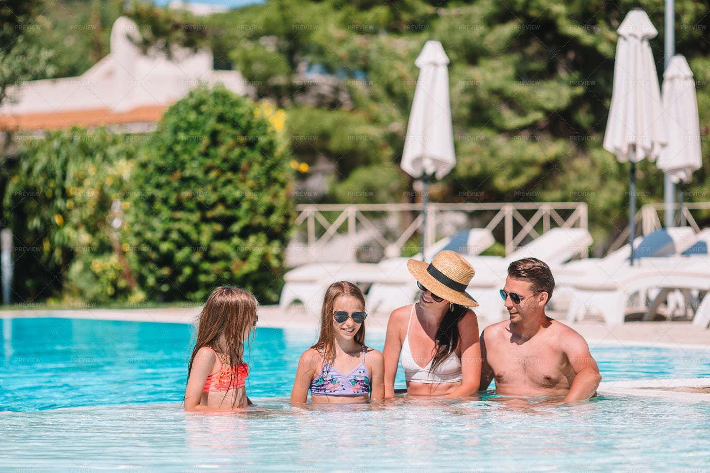 Happy Family Of Four In A Pool: Stock Photos