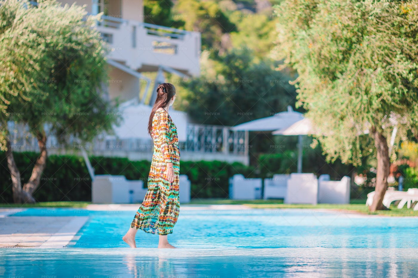Woman Walking Next To Swimming Pool: Stock Photos