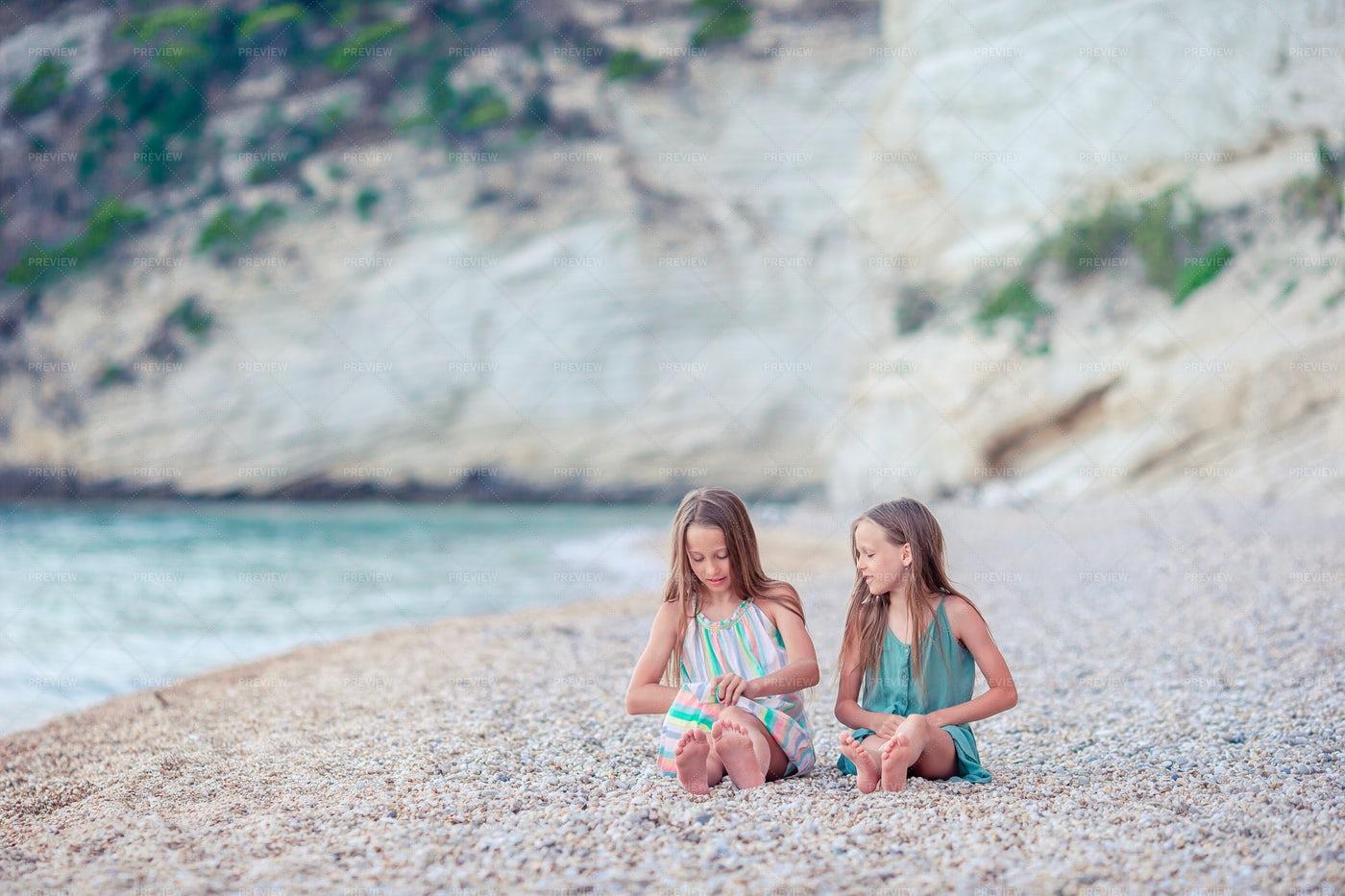 Sisters Sitting On Beach: Stock Photos