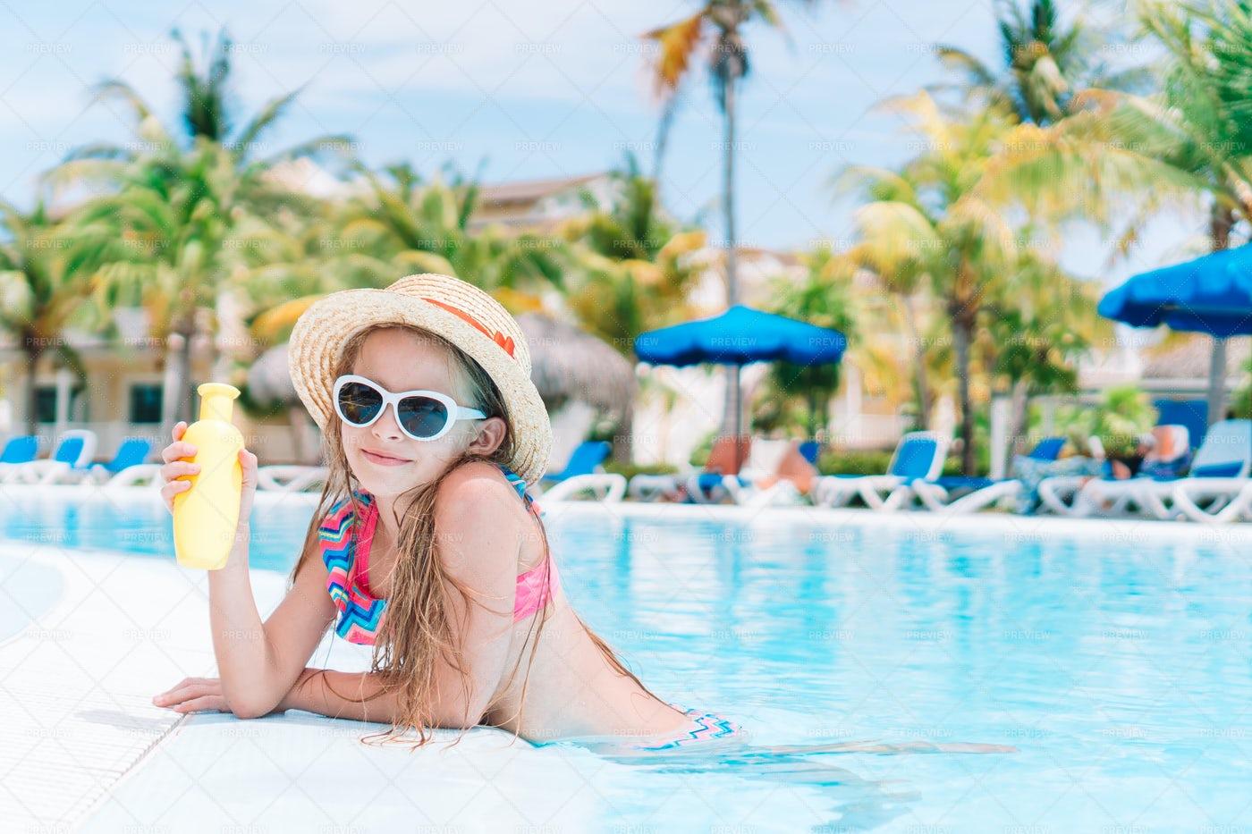 Little Girl With Bottle Of Sun Cream: Stock Photos