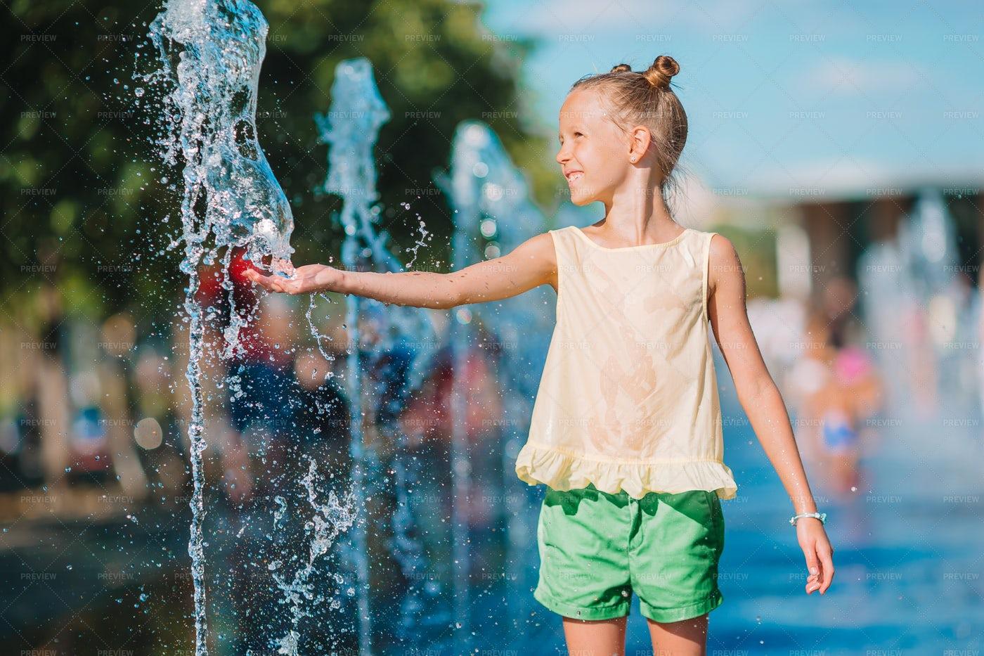 Girl Touching Water Fountain: Stock Photos
