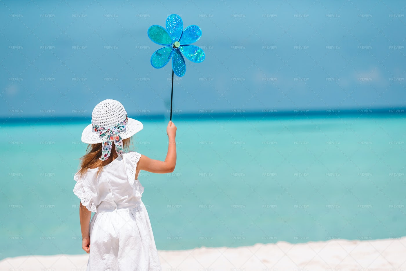 Girl With A Flower Windmill Toy: Stock Photos