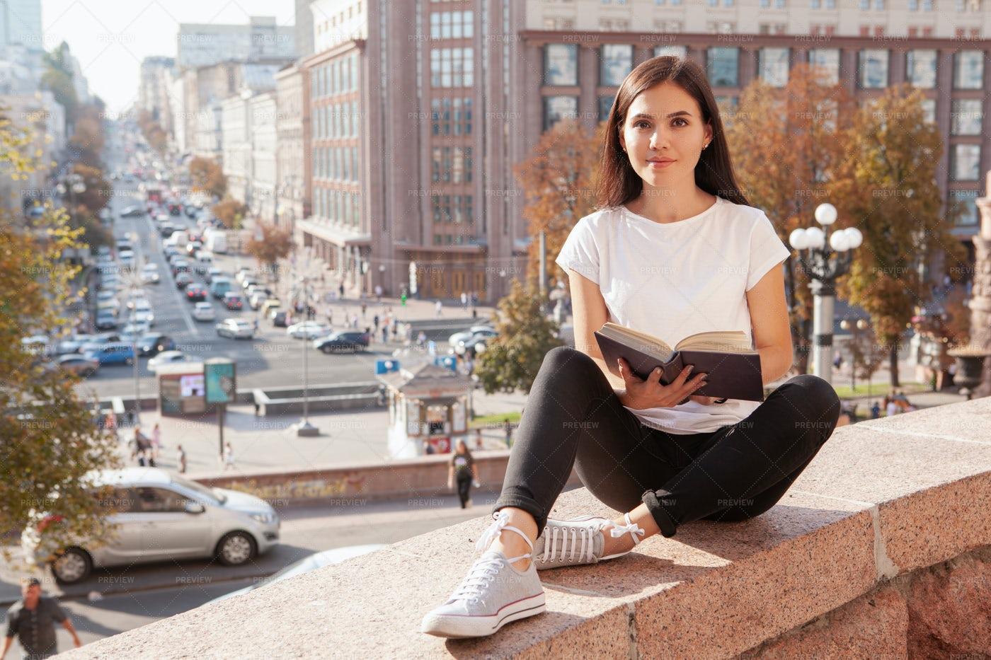 Woman Reading Book At Urban Center: Stock Photos